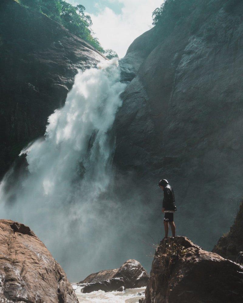 Person standing at a waterfall